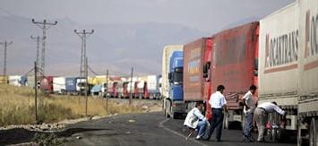 les chauffeurs se reposent près de leurs camions transportant des marchandises en Irak à la frontière Turque mercredi.